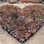 A crowd of people standing in a heartshape